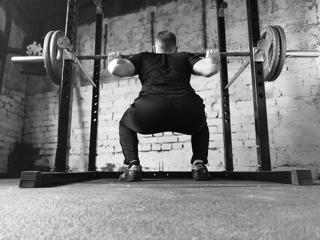 homme qui fait des squats à la musculation